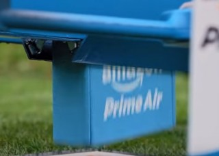 In this still from the commercial, the drone appears to be . . . expelling a product purchased on Amazon. (via YouTube)