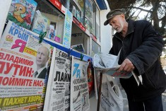 An elderly man looks through a newspaper at a kiosk with Russian newspapers displayed outside in the Crimean port of Sevastopol on March 27, 2014. The Crimean crisis has sparked the most explosive East-West confrontation since the Cold War and fanned fears in Kiev that Russian President Vladimir Putin now intends to push his troops into southeast Ukraine. AFP PHOTO/ VIKTOR DRACHEV